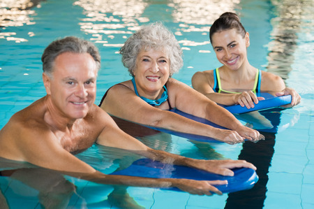 Happy senior couple taking swimming lessons from young trainer. Smiling old woman and mature man doing aqua aerobics exercise in swimming pool. Retired people in swimming pool looking at camera. Stock Photo