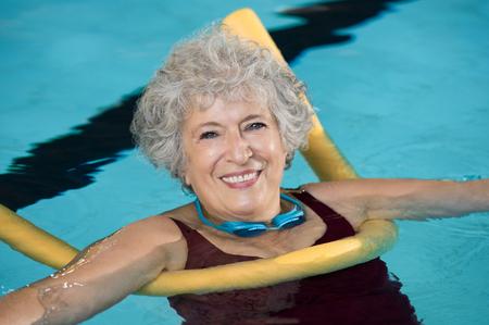 泳ぐ麺とアクアのフィットネスをしている年配の女性。成熟した女性の黄色い麺とウォーター ・ エアロビクスを行います。Aquarobic とリハビリ運動