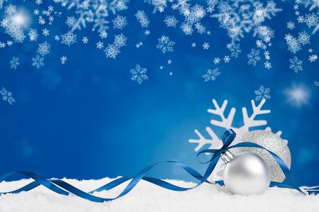 Blaue Verzierung mit weißen Schnee und Schneeflocke auf glänzenden blauen Hintergrund. Weihnachten Hintergrund mit Silber und glänzenden Kugeln mit blauem Band und Kopie Raum. Weihnachten Urlaub und blaue Dekoration auf weißem Schnee.