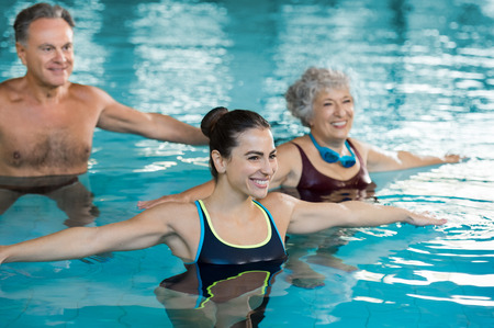 Smiling fitness class doing aqua aerobics in swimming pool. Smiling young woman with senior couple stretching arms in swimming pool while doing aqua aerobics. Fit mature man and old woman exercising in swimming pool with young woman.