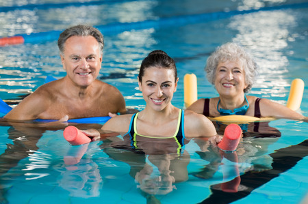 Happy mature man and old woman doing aqua aerobics with foam rollers in swimming pool. Senior couple smiling with swim noodles doing aqua fitness. Smiling young trainer with mature class doing aqua gym fitness. Stock Photo
