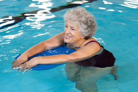 Happy senior woman with kickboard in a swimming pool. Old woman swimming in water with the help of a kickboard. Smiling old woman swimming with inflatable board in swimming pool. Stock Photo