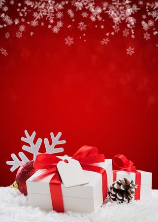 Cierre de caja pequeña de Navidad con cinta roja y tarjeta de felicitación vacía. Decoración de Navidad con bola brillante y cono de pino en la nieve. Navidad fondo rojo vertical.