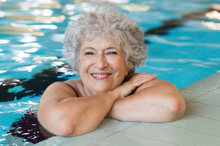 Portrait der älteren Frau gegen den Rand eines Swimming-Pool und Blick in die Kamera. Fit und aktive Senior Frau genießen den Ruhestand im Schwimmbad. Schöne reife Frau Entspannung im Schwimmbad.