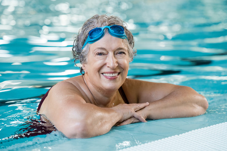 swimming: Mature woman wearing swim goggles at swimming pool. Fit active senior woman enjoying retirement standing in swimming pool and looking at camera. Happy senior healthy old woman enjoying active lifestyle. Stock Photo