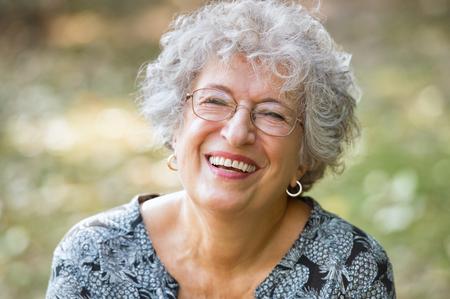 Portret van senior vrouw glimlacht en kijkt naar de camera. Vrolijke rijpe vrouw met bril in het park. Gelukkige oude vrouw met grijs haar lachend. Zorgeloos en positieve gepensioneerde vrouw.