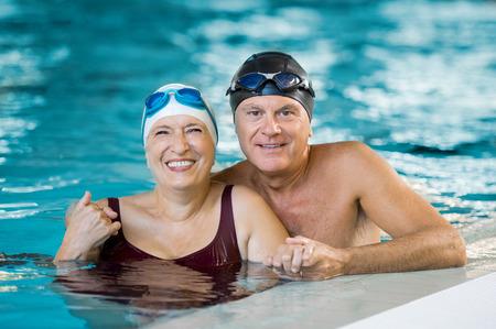 Porträtt av ett äldre par badar i poolen och tittar på kameran. Leende mogen man och gammal kvinna njuter av tiden tillsammans i en pool. Glad pensionerad par efter vattengympa.