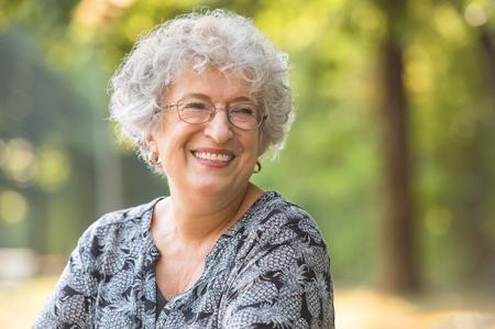 mujeres ancianas: Retrato de la sonrisa mujer mayor con gafas en el parque. Mujer mayor de risa que mira lejos. Feliz thoughful relajante al aire libre de la mujer madura. Anciana jubilada activa. Foto de archivo