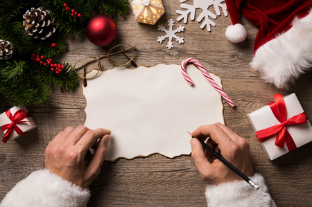 letter: Top view of christmas letter in santa claus hand. Close up of hands holding empty wishlist on wooden table with xmas decoration. High angle view of santa claus hands writing on a paper with gift boxes and fir branch on table.