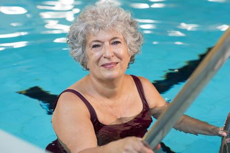 Sonriente mujer mayor activo que entra en una piscina. Sonrisa anciana mirando a la cámara antes de la lección aeróbicos en el agua. Feliz mujer madura lista para nadar.