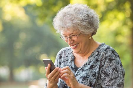 Lachende oudere vrouw met een bril en het typen van telefoon bericht tijdens de vergadering op park. Vrolijke senior vrouw met behulp van draadloze internet verbinding op slimme telefoon tijdens het schrijven van een sms. Gelukkig bejaarde vrouw kijkt naar het scherm op de smartphone.