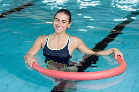 La mujer sonriente feliz haciendo ejercicio con tubo de aqua en una piscina. mujer juguetona joven que ejercita en la piscina con la ayuda de un tubo. Mujer heallthy joven que hace aeróbicos en la piscina. Foto de archivo - 64821204