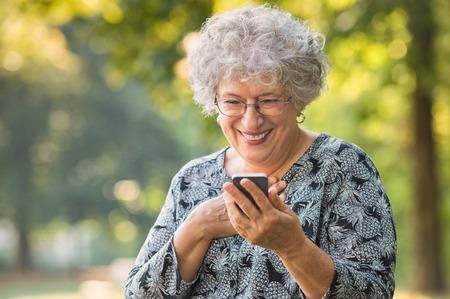 명랑 한 여자 스마트 폰을 통해 좋은 소식을 받고 흥분. 행복 한 고위 여자 공원에서 휴대 전화를 사용 하여. 귀여운 할머니는 그녀의 사랑에 대 한 메 스톡 콘텐츠