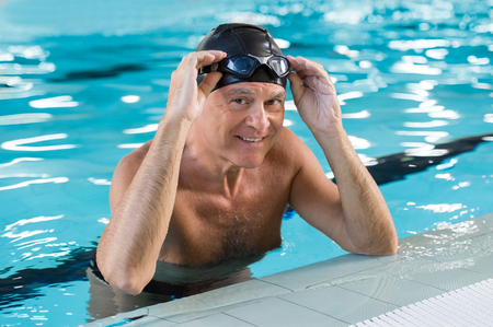 Smiling old man in a swimming pool wearing swim cap and goggles on his head. Portrait of a satisfied senior man after swimming in the pool. Retired proud man leaning at the poolside looking at camera.