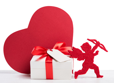Close up of small gift box for valentine day isolated on white background. Valentine present with greeting card and red cardboard heart shape. Love valentine day with cupid and romatic gift box wrapped in red ribbon.