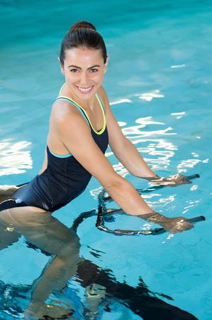フィット笑顔の女性は、スイミング プールでアクアの自転車でサイクリングします。スイミング プールの水エアロバイクの下を使用して笑顔の若い