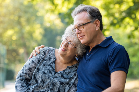 leans: Portrait of a loving mature couple embracing at park. Senior couple sitting outdoor and thinking about retirement. Old man embracing elderly woman while she leans her head on his shoulder. Stock Photo