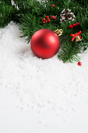 Close up of xmas decoration with white snow and fir branch. Vertical composition of christmas red ball with little bell and pine cone. Red ball on christmas tree with copy space.
