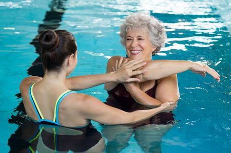Young trainer helping senior woman in aqua aerobics. Senior retired woman staying fit by aqua aerobics in swimming pool. Happy old woman stretching in swimming pool with young trainer. Stock Photo