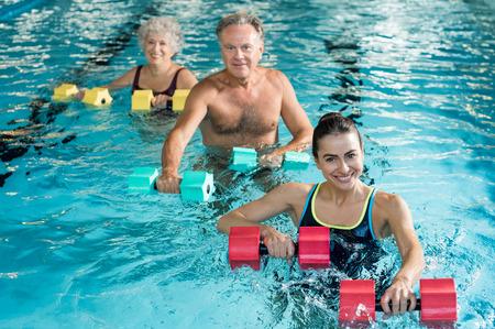 Happy aktivní fitness zralý muž a starší žena, která dělá cvičení s aqua činky v bazénu s instruktorem. Důchodci dělají aqua fitness cvičení s jednoručkami vody v bazénu a díval se na kameru.
