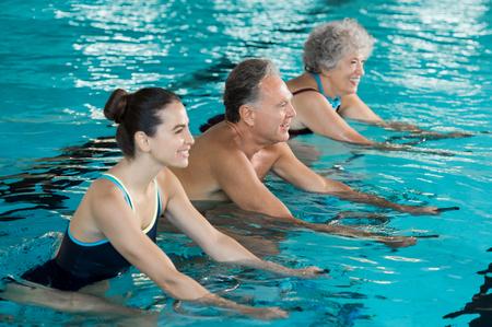 gimnasia aerobica: sonriendo Feliz el hombre maduro y una mujer de edad andar en bicicleta en una bicicleta nadar en la piscina. las personas mayores felices y saludables disfrutando de la natación con la mujer joven. Clase de la aptitud que hace aeróbicos aqua en bicicletas de ejercicio en una piscina. Foto de archivo