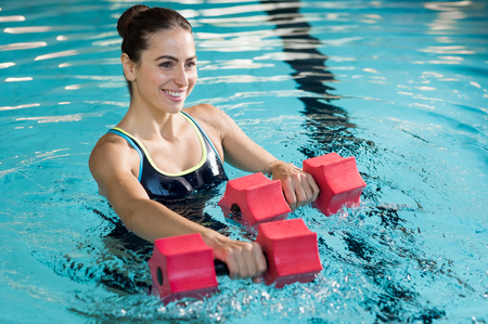 Mulher apta que elabora com dumbbell espuma na piscina no centro de lazer. Mulher envolvida em fazer hidroginástica em água. Mulher bonita nova que faz do Aqua exercício da ginástica com dumbbell da água na piscina. Imagens