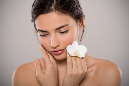 Beautiful woman with white flower looking down isolated on grey background. Close up face of young woman holding delicate orchid flowernear face. Emotional and sensitive girl looking inside herself.