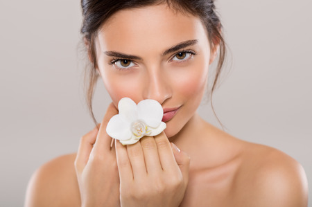 Portrait of a beautiful woman with bare shoulders holding a flower of orchid isolated on grey background. Portrait of natural beauty of young woman holding white orchid flower near face and looking at camera. Stock Photo