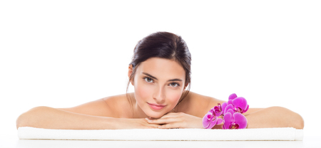 Beautiful woman relaxing on towel with purple orchid flower isolated on white background. Portrait of young woman enjoying massage while smiling. Banner of brunette girl lying down on front and looking at camera. Stock Photo