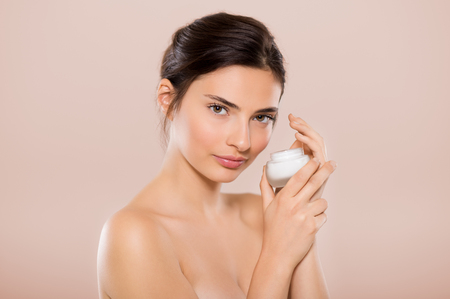 Beautiful woman holding jar of skin cream for face and body isolated on beige background. Brunette woman applying cosmetic moisturizer and looking at camera. beautiful woman showing small jar of moisturizing lotion.