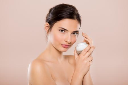 Mooie vrouw die pot van huidcrème voor gezicht en lichaam op een beige achtergrond houdt. Brunette vrouw die cosmetische moisturizer toepast en camera kijkt. mooie vrouw met kleine potje hydraterende lotion.