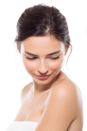 Junge schöne Frau mit perfekter Haut nach unten. Close up Gesicht der jungen Frau Schönheit. Junge schöne Frau Gefühl schüchtern auf weißem Hintergrund. Wellness und Hautpflege-Konzept. Standard-Bild