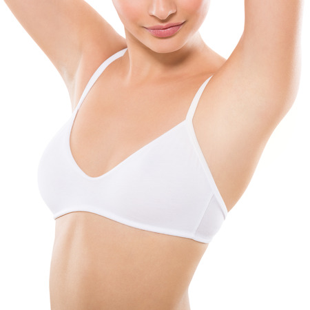 Closeup of a beautiful young woman showing her smooth armpit isolated on white background. Girl holding her arms up and showing clean underarms. Hairs removal and depilation concept. Banque d'images
