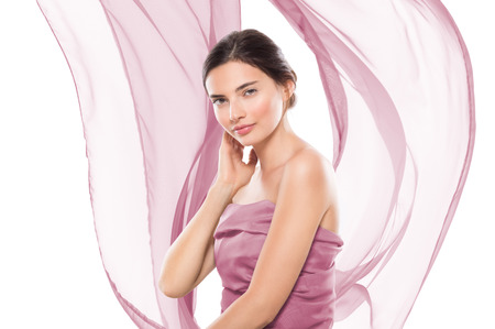 Portrait of a young beautiful woman wrapped in violet cloth isolated on white background. Young pure woman looking at camera with hand on cheek. Glamour girl with pink flowing scarf with copy space. Stock Photo