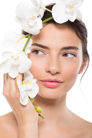 Closeup face of beautiful young woman with orchid flower looking away. Portrait of beauty girl holding flowers near face isolated on white background. Beauty treatment and skin care concept.