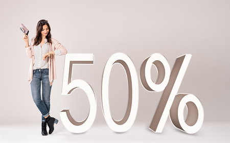 percent: Happy young fashion woman wearing jacket leaning at seasonal sales. Fashion girl holding clutch purse in hand and looking the offer. Beautiful glamour girl standing on grey background with amazing sale and promotion.