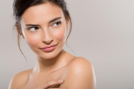 Close up face of beautiful young woman with healthy clean skin isolated on grey background looking away. Portrait of brunette girl smiling, copy space. Beauty and spa treatment.