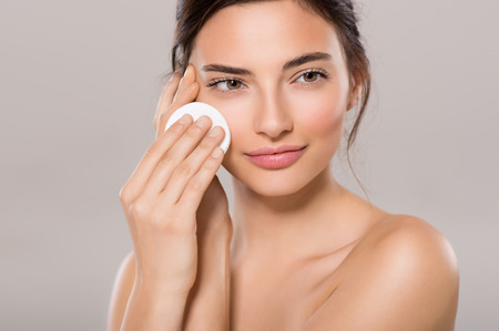 removing: Healthy fresh girl removing makeup from her face with cotton pad. Beauty woman cleaning her face with cotton swab pad isolated on grey background. Skin care and beauty concept.