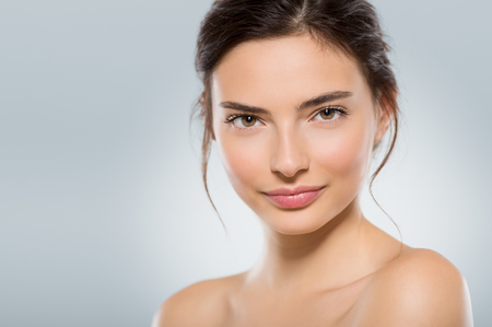 Beautiful face of a young woman with clean fresh skin isolated on light blue background. Close up face of natural gil after beauty treatment looking at camera. Skincare and body care concept.