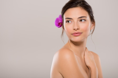 Beautiful woman with pink orchid flower in her hair looking away with copy space. Beautiful face of a young and healthy woman with bare shoulders isolated on grey backgroud. Body care and spa treatment.
