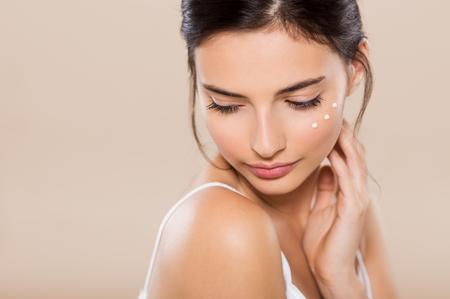 mujeres morenas: Mujer joven mirando hacia abajo con la cara crema hidratante cerca de los ojos. Mujer hermosa que aplica la loción de la cara en la mejilla. chica morena hermosa con íntima perfecta y saludable sensación de la piel tímida aislada en el fondo caliente.