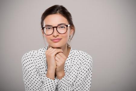 복사 공간이 회색 배경에 고립 된 현대 안경 anf 생각을 입고 젊은 여자. 큰 안경을 착용하는 웃는 패션 학생의 초상화입니다. 자랑스럽게 젊은 사업가