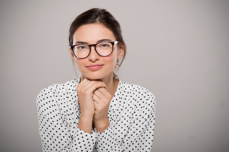 Jonge vrouw die de moderne bril ANF denken op een grijze achtergrond met een kopie ruimte. Portret van glimlachende fashion student het dragen van grote glazen. Trotse jonge zakenvrouw met een bril kijken naar de camera.