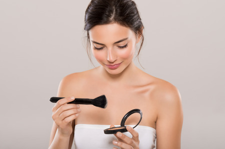 Portrait of a young beautiful woman applying foundation with black brush. Young woman holding face powder box on grey background. Woman holding make up blush and smiling.