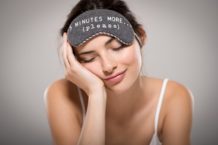 resting mask: Young beautiful woman sleeping with eye mask on grey background. Portrait of brunette tired girl with eye mask for sleeping. Sleepy beauty woman resting on hand with closed eyes.