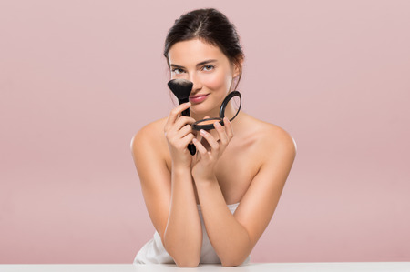 Young beautiful woman holding foundation box and brush while leaning on white table. Smiling woman holding blusher box isolated on pink background. Beauty brunette girl having fun and joking with make up and face powder.