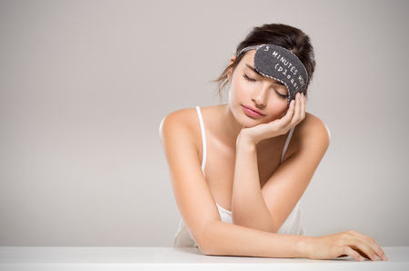 Sleepy woman with sleeping on table with copy space. Beauty young woman in pajamas smiling and sleeping with eye mask on head. Tired woman resting and dreaming with sleeping mask isolated on grey background. Stock Photo