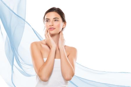 spas: Junge Frau sucht weg, während ihr Gesicht auf weißem Hintergrund zu berühren. Schönheit Brunette Mädchen Gefühl frisch nach Spa-Behandlung mit Kopie Raum auf der rechten Seite und blauen Wellen von Tüchern. Schönheit und Hautpflege-Therapie.