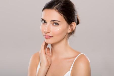 Mladá žena použití hydratační krém na obličej izolovaných na šedém pozadí. Krásná žena použití kosmetického krému na kůži v blízkosti očí a díval se na kameru. Koncepce krásy a péče o pleť.