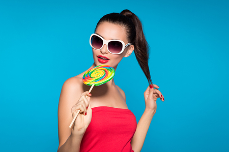 Young beautiful woman holding lollipop isolated on blue background. Happy brunette girl wearing red top and sunglasses eating multi colored candy. Sexy joyful and cheerful woman eating lollypop having fun.